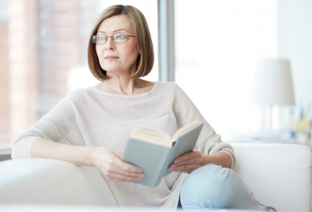 serious: Charming mid age lady enjoying being at home and reading