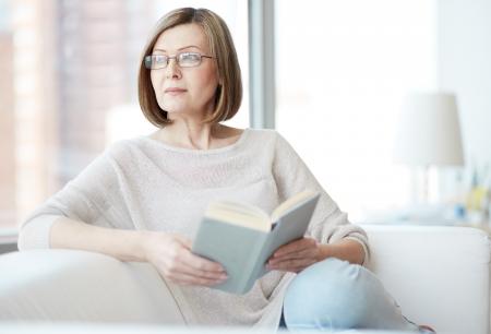 mujeres pensando: Mediados mujer de edad con Encanto disfrutando de estar en casa y leer