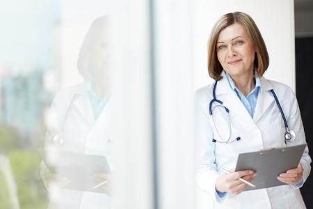 医療記録を保持しているフレンドリーな一般開業医の肖像画のコピー間隔