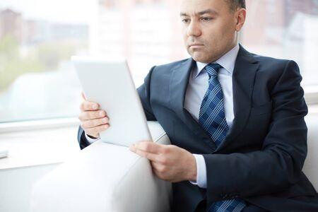 business men: Image of a mature entrepreneur choosing the most suitable business solution via tablet