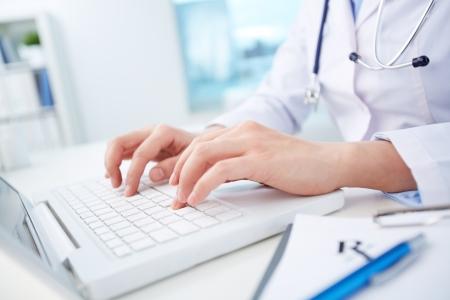 노트북을 통해 의료 기록을 공부하는 여성 의사의 총을 닫습니다