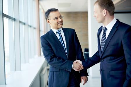 integrity: Portrait of elegant businessmen handshaking in conference hall Stock Photo