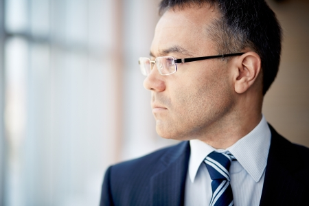Portrait of thoughtful businessman looking through window photo