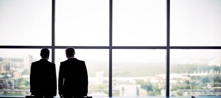 Silhouetten van twee zakenlieden staande bij het raam