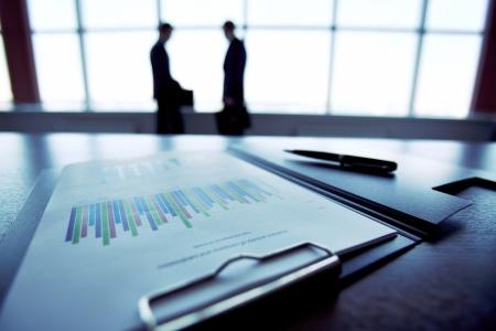informe comercial: Primer plano de un informe financiero con las siluetas de la gente de negocios en el fondo