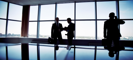 Business people spending a usual busy day in office, only silhouettes being recognizable photo