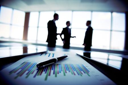 Equipe: L'image ombragé d'une équipe d'affaires discuter des derniers résultats financiers Banque d'images
