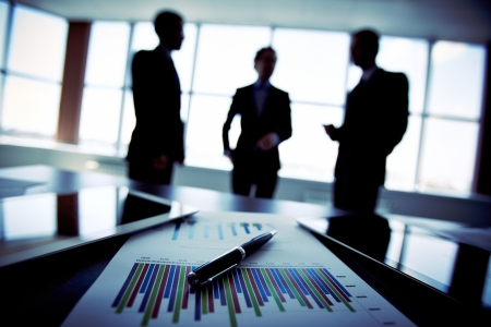 strategic focus: Shadowy business trio holding a briefing concerning the reported statistic data