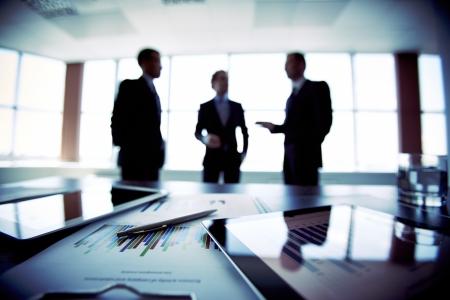 Collega's bijeen om hun toekomstige financiële plannen te bespreken, slechts silhouetten worden bekeken Stockfoto