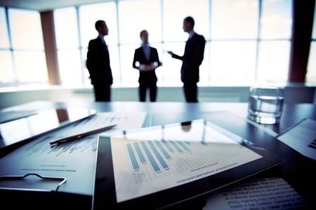 trabajo en oficina: Primer disparo de un equipo Tablet PC que muestra los datos financieros, tres empresarios de pie en el fondo