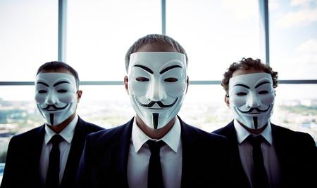Ritratto di tre persone che indossano maschere anonime Editoriali