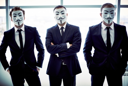 Portret van drie collega's zich te verschuilen achter Guy Fawkes maskers