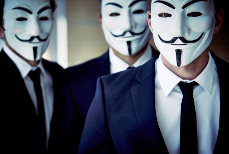 vendetta: Close-up portrait of unrecognizable people wearing Guy Fawkes masks and business suits