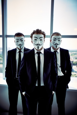 vendetta: Vertical portrait of young business workers covering their faces with anonymous masks