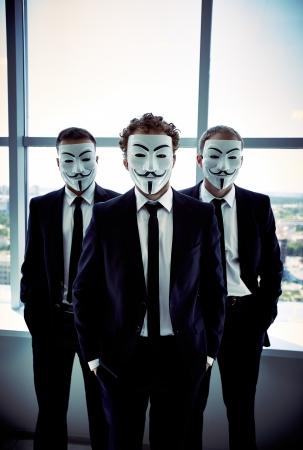 Verticale portret van jonge business werknemers die hun gezicht met anonieme maskers