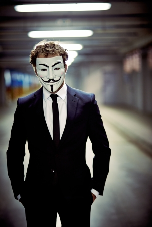 Vertical portrait of a business guy staring from behind anonymous mask