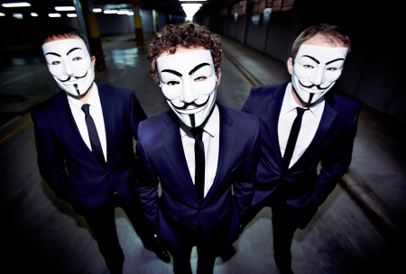 fawkes: Portrait of three guys in Guy Fawkes masks with intense looks and formal appearance