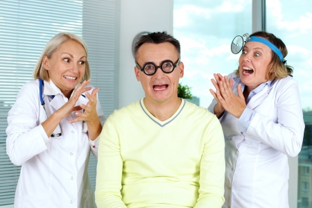 terrified: Portrait of a patient being scared of the doctors rubbing their hands with scary enthusiasm Stock Photo