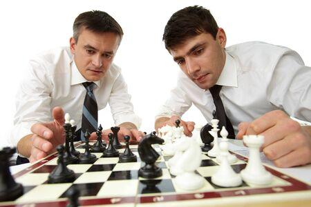 pensamiento estrategico: Aislado imagen de hombres de negocios serios que desarrollan su pensamiento estrat�gico, jugando al ajedrez Foto de archivo