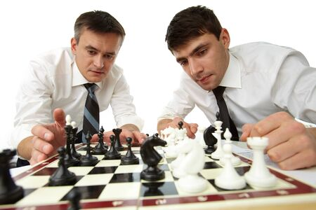 Isolated image of serious businessmen developing their strategic thinking by playing chess photo