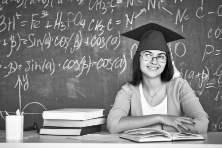 Black-and-white image of student in graduation hat and eyeglasses looking at camera on background of chalkboard