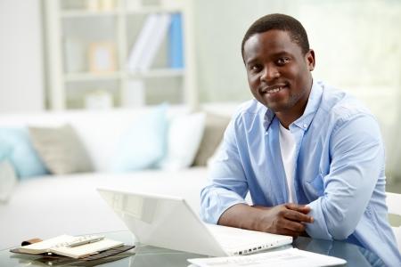ノート パソコンの近くでカメラを見てアフリカ青年のイメージ