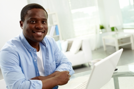 Image of young African man looking at camera with laptop near by Stock Photo - 21063321