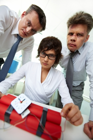 human time bomb: Group of businesspeople looking at camera with dynamite on workplace