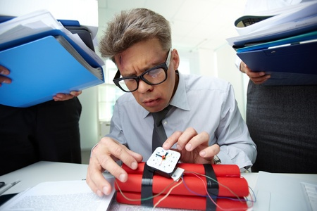 Mature accountant with dynamite being surrounded by colleagues with big heaps of papers Stock Photo - 21063348