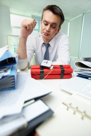 Experienced businessman with cigarette looking at dynamite Stock Photo - 21063352
