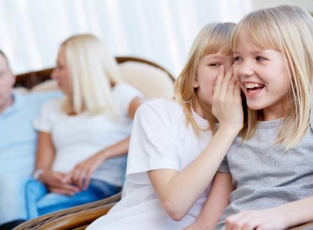 soeur jumelle: Portrait d'une jeune fille heureuse de rire tandis que sa soeur jumelle chuchoter quelque chose � son Banque d'images
