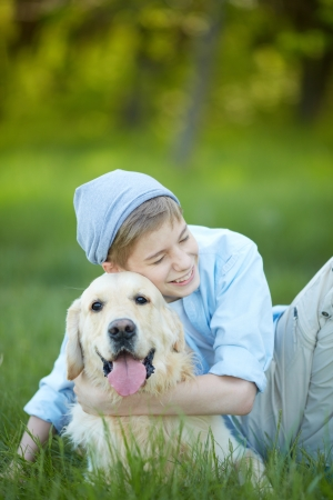Portrait of cute lad embracing his fluffy friend and laughing    Stock Photo