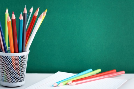 copybook: Stack of colorful pencils and open copybook near by on background of blackboard