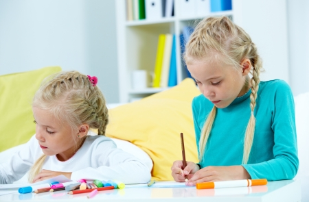 Portrait of lovely twins drawing with colorful pencils photo