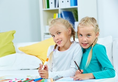 twin sister: Portrait of lovely twins with colorful pencils looking at camera