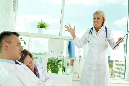 displeased: Tired clinicians in white coats sleeping in office while displeased doctor looking at them Stock Photo