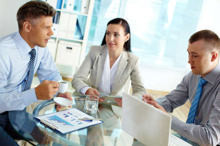 Boardroom meeting: Positive business people discussing strategy or planning work in office