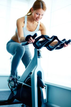 Image of young female training on simulator in gym Stock Photo - 21063484