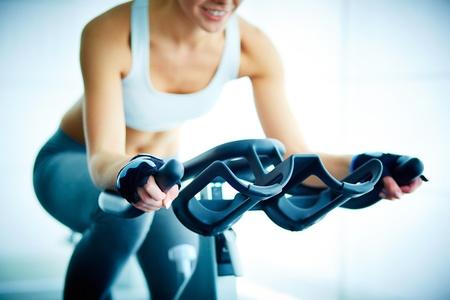 gimnasio: Primer plano de la formaci�n femenina joven en simulador en el gimnasio