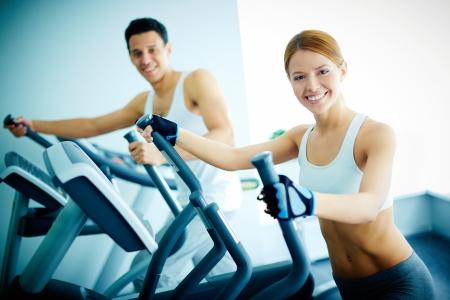 Portret van mooi meisje en jonge kerel training op speciaal sportmateriaal in sportschool Stockfoto