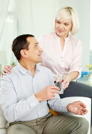 taking pill: Portrait of senior woman giving a glass of water to her husband