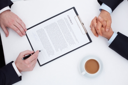 Image of businessman hands signing contract with his partner hands near by photo