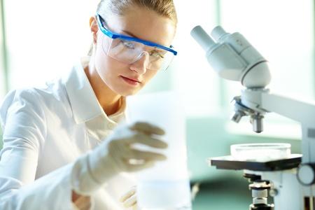Serious female chemist working in laboratory Imagens
