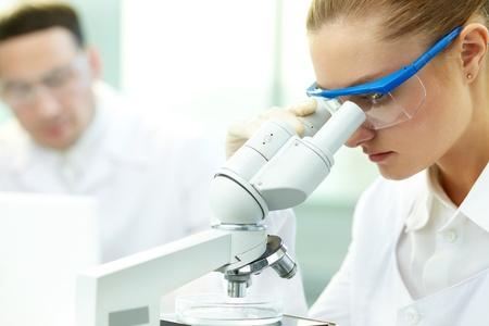Ernstige arts het bestuderen van chemisch element in het laboratorium