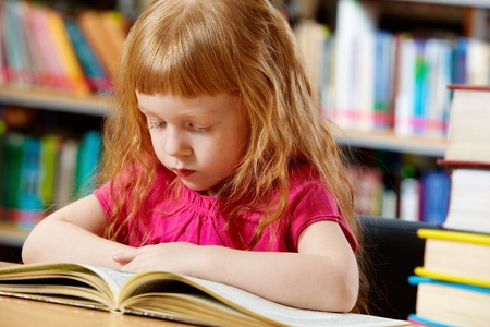 culture school: Portrait of smart girl reading book in library