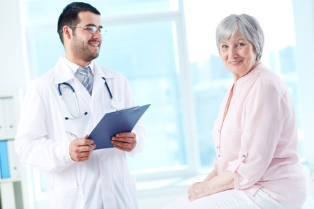 Confident doctor with stethoscope and clipboard looking at his senior patient photo