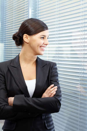 neighbouring: Image of formal businesswoman in suit looking through jalousie into neighbouring office Stock Photo