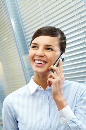 Image of young pretty secretary talking by cellular phone in office Stock Photo - 21174346