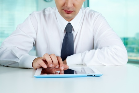 Close-up of businessman working with digital tablet at workplace photo