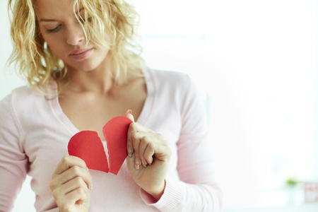 Sad female tearing up red broken paper heart Stock Photo